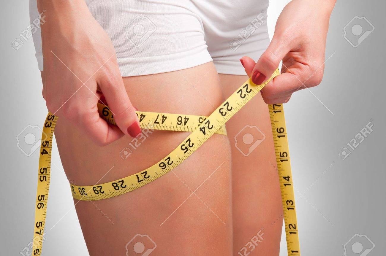 Woman measuring her thigh with a yellow measuring tape Stock Photo - 19668897