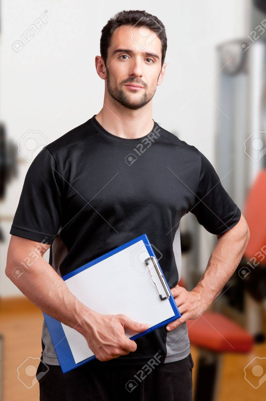 Personal Trainer, with a pad in his hand, in a gym Stock Photo - 19802325