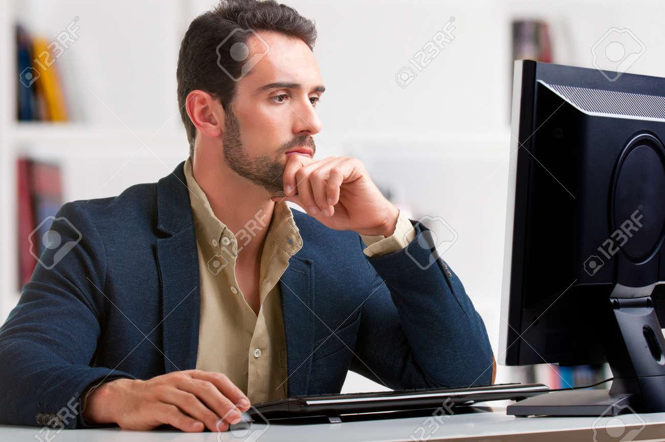 Man looking at a computer screen, thinking about the job at hand Stock Photo - 19877100