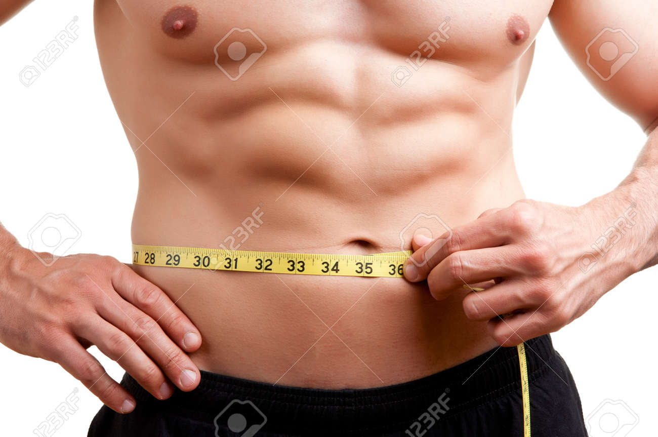 Fit man measuring his waist after a workout in the gym, isolated in a white background Stock Photo - 19877092
