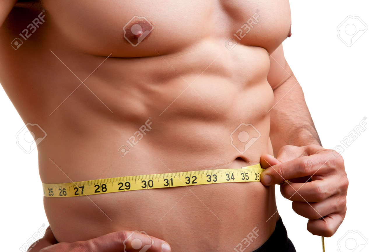 Fit man measuring his waist after a workout in the gym, isolated in a white background Stock Photo - 19855380