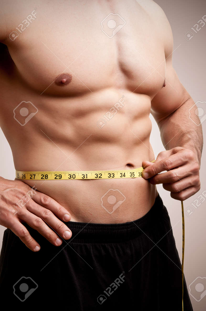Fit man measuring his waist after a workout in the gym, in a dark brown background Stock Photo - 20043927