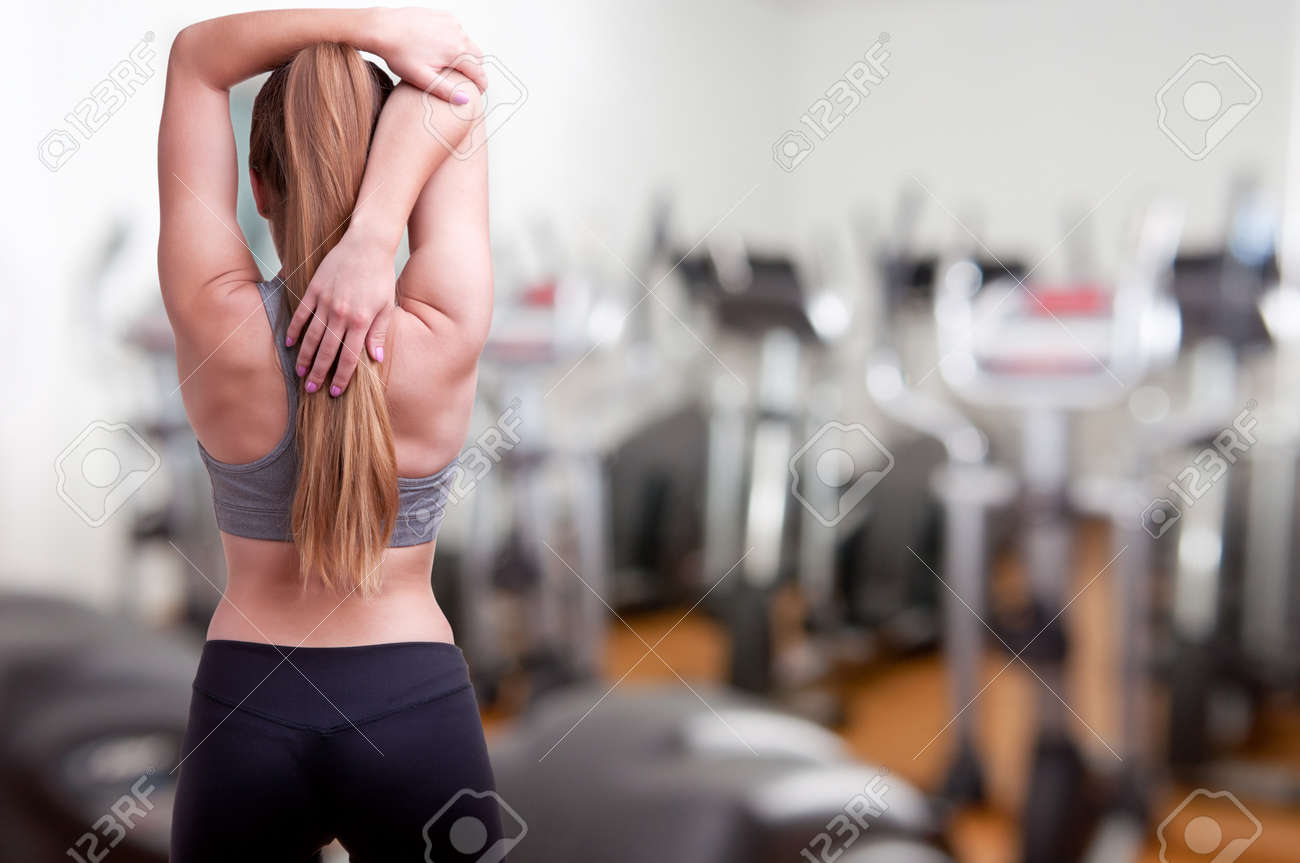Sporty woman stretching her arm, in a gym Stock Photo - 20484319