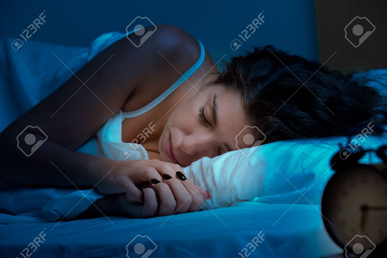 Woman sleeping in a bed in a dark bedroom Stock Photo - 33444664