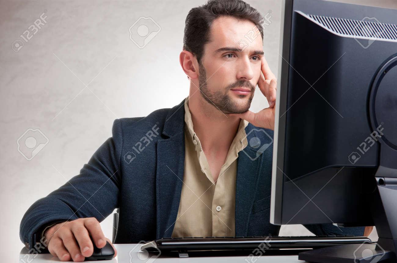 Man looking at a computer screen, thinking about the job at hand Stock Photo - 43048480