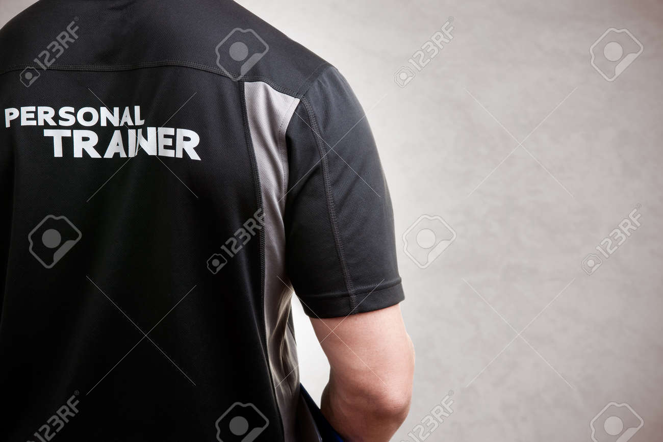Personal Trainer, with his back facing the camera, in a grey background Stock Photo - 43048489