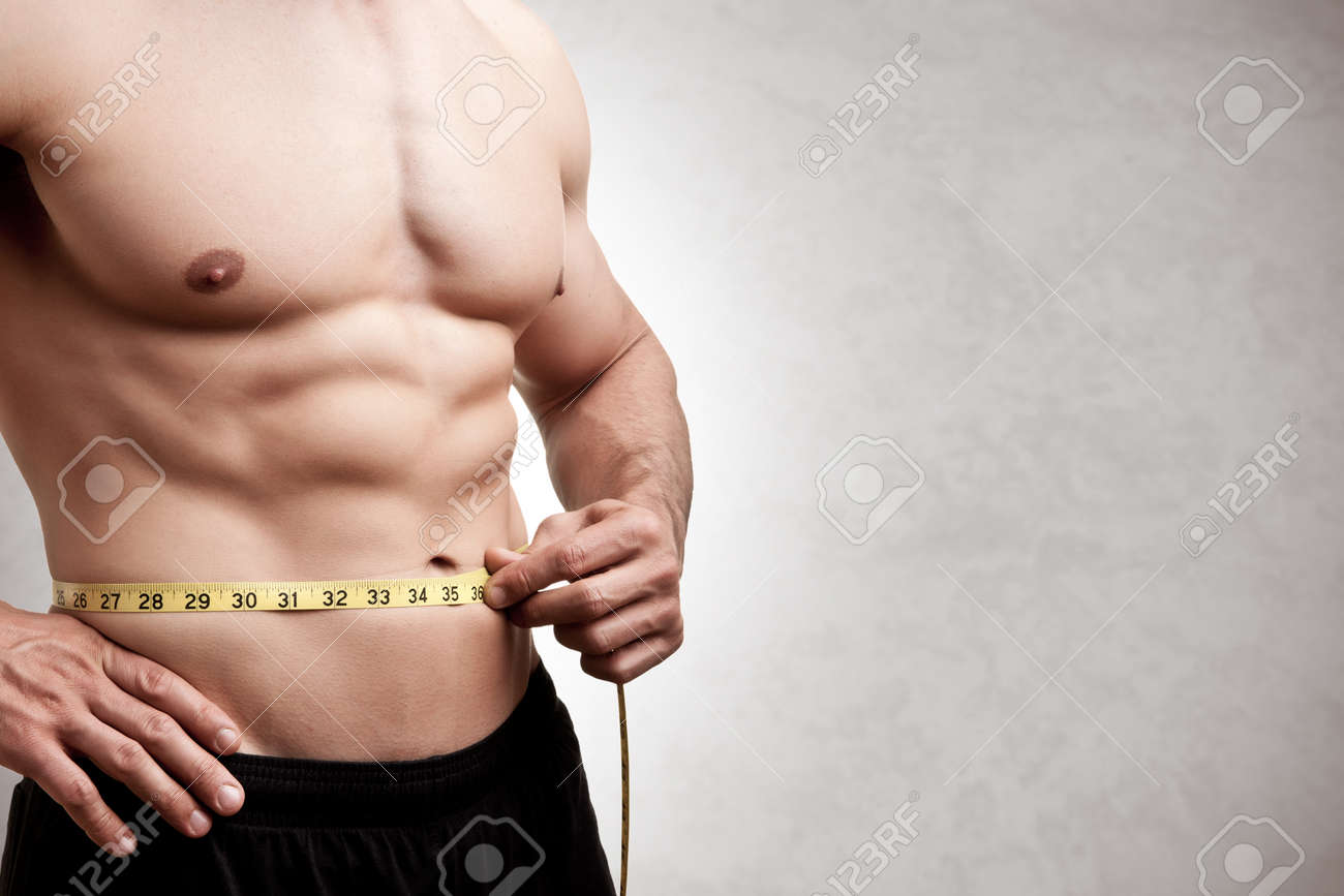 Fit man measuring his waist after a workout in the gym, isolated in a grey background Stock Photo - 43048608