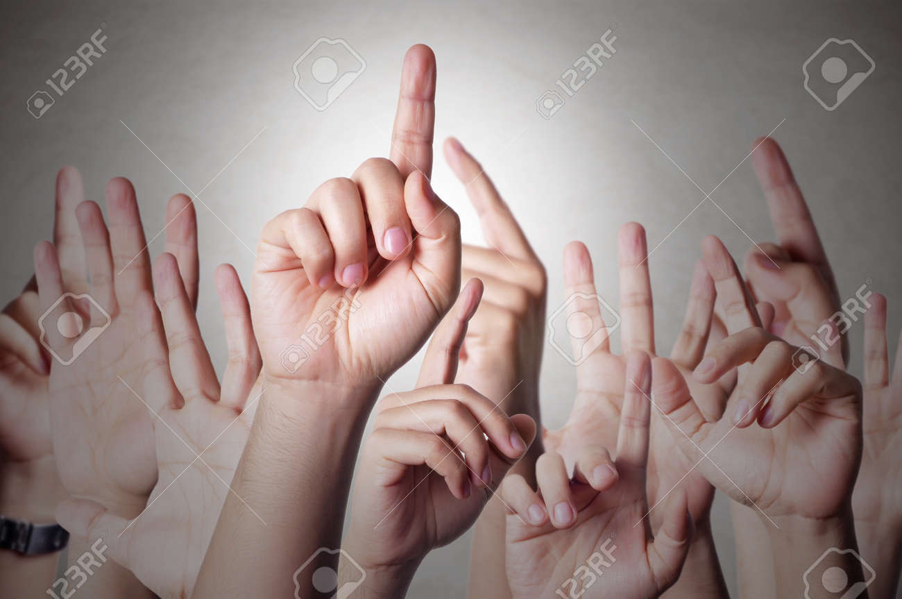 Group of people raising hands to answer a question Stock Photo - 43048616
