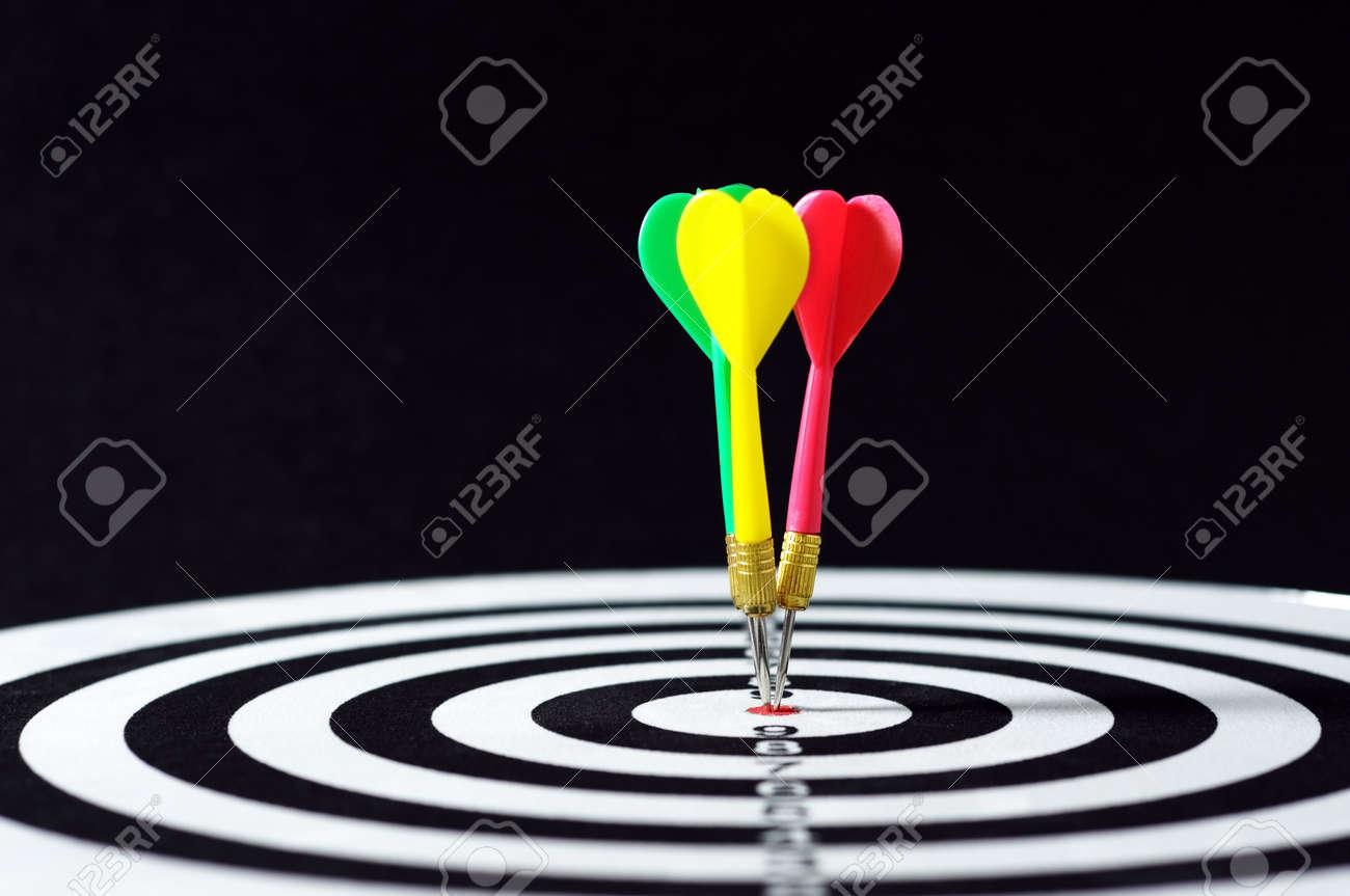 Three darts on target  horizontal shot with black background