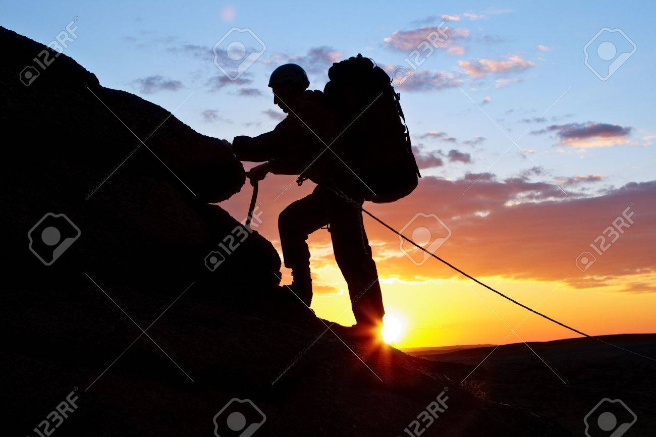 The climber goes uphill on sunset Stock Photo - 10751255