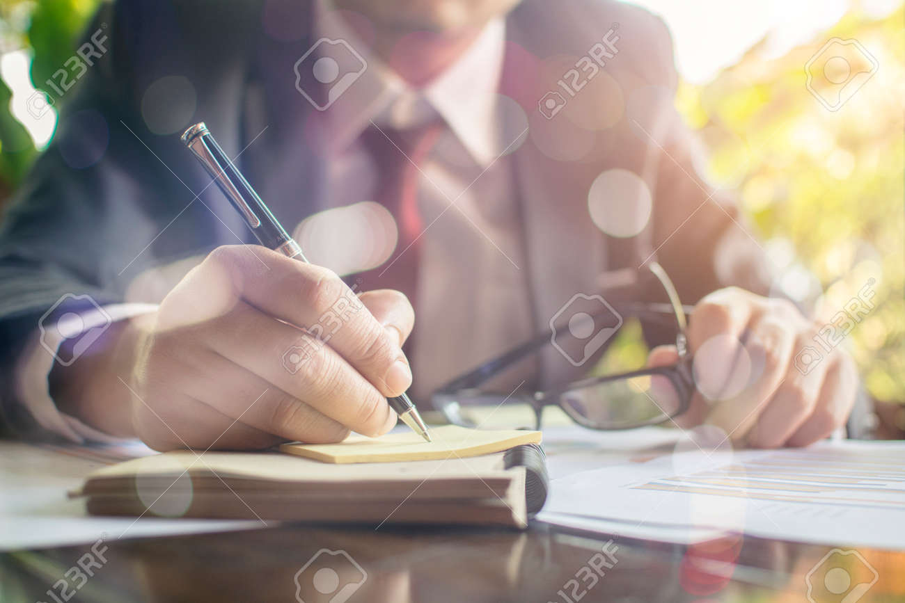 Businessman check seriously analyzes a financial reports and writing on notebook on wooden table at office Finance managers task Concept business and finance - 84167183