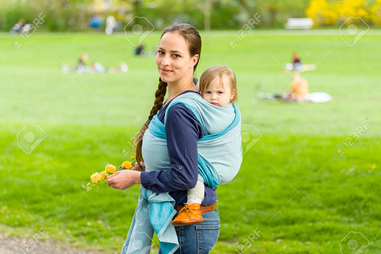 8343e6b23df A young mother carrying her little baby in a sling on her back and walked in