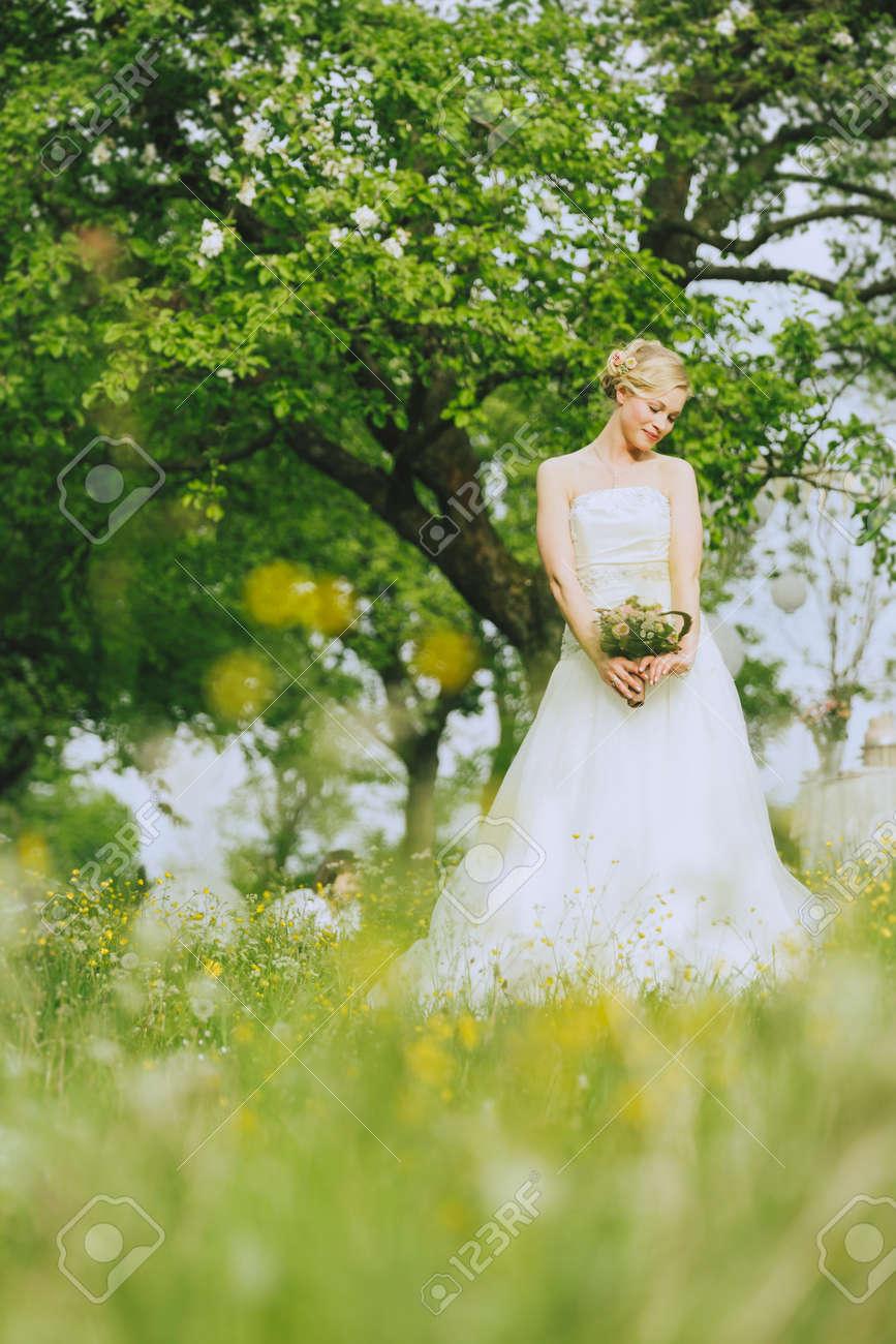 Die Braut Im Weissen Hochzeitskleid Steht In Der Landschaft Auf Einer