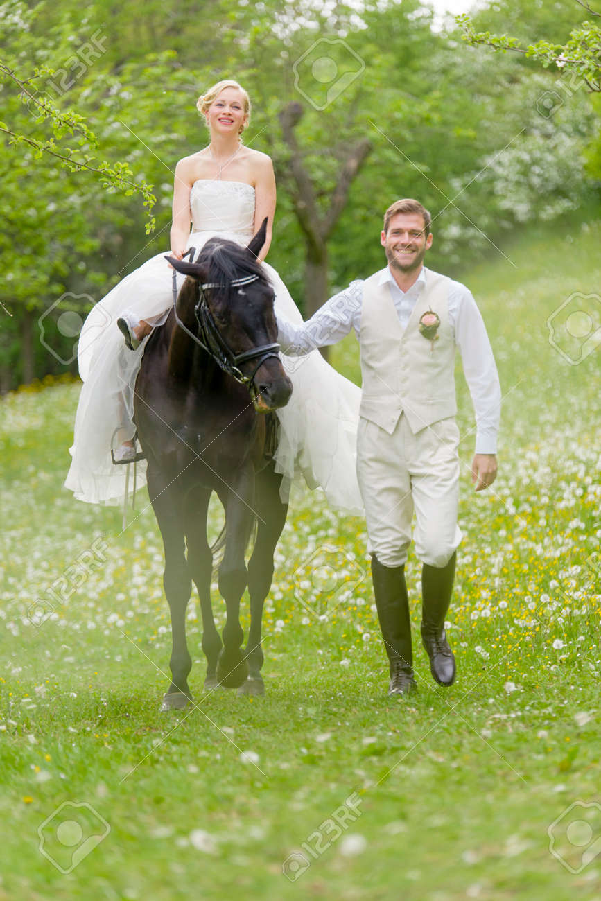 cheaper 85cb5 2f171 Matrimonio in campagna. La sposa nel suo abito da sposa bianco si siede su  un cavallo scuro ed è guidato dal suo sposo ridere sul prato fiorito.