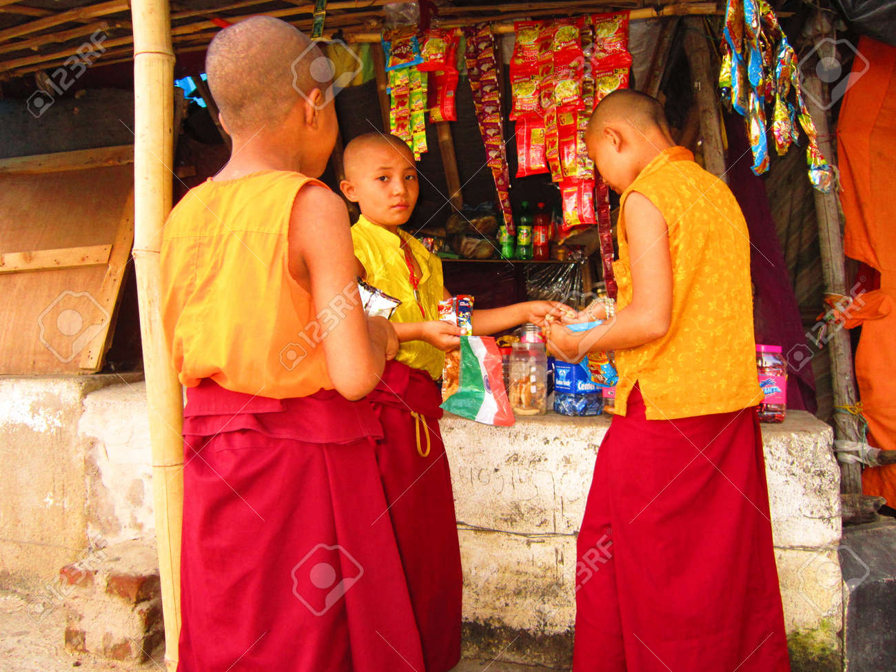 Children monk with INDIAN NATIONAL FLAG ahead of Independence day of India at a grocery shop in front of Karma Monastaery, Bodhgaya, Shot at 1754 pm on 11.08.12 at Bodhgaya, Bihar, India, Asia. Stock Photo - 14816216