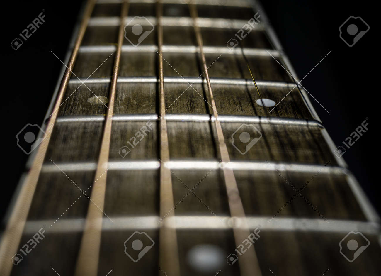 A closeup shot of a guitar fretboard using shallow depth of filed and black background. - 152581385
