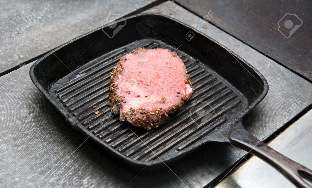 Tasty beef steak grilling in a cast-iron ribbed fry pan Stock Photo - 6238842