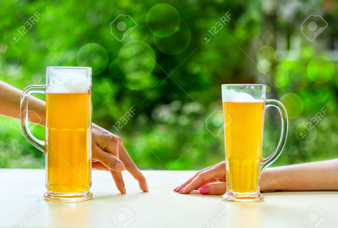 two hands, man and woman with beer in glass Stock Photo - 6871032