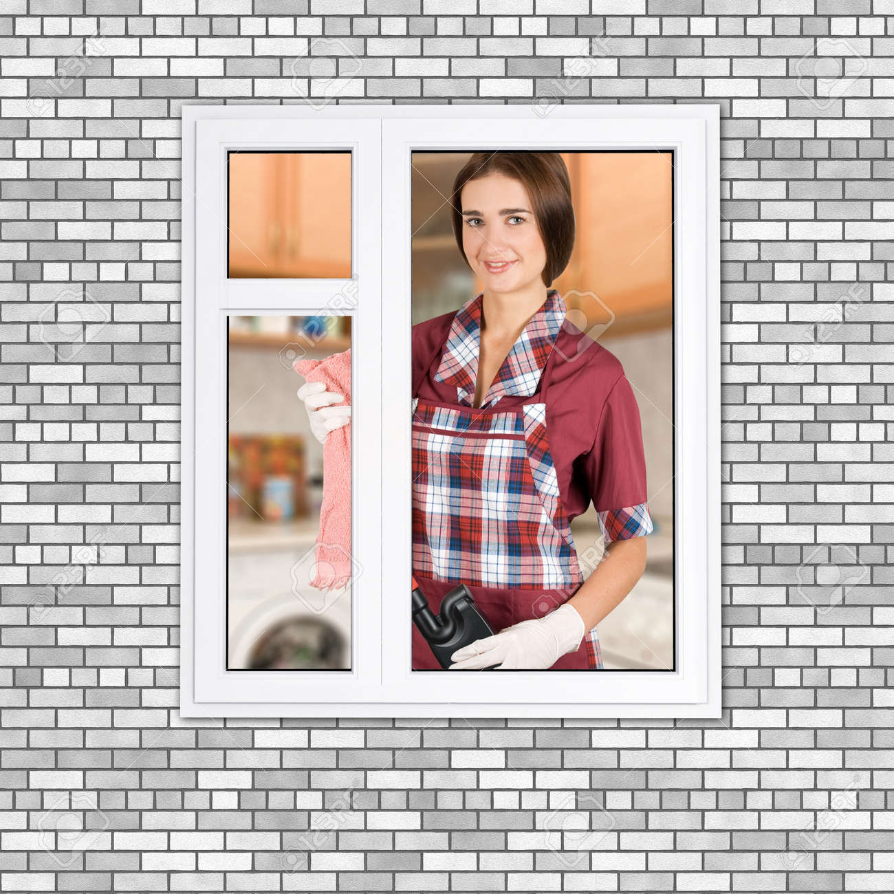 Young girl with a pack of detergents cleaning a window Stock Photo - 8006876