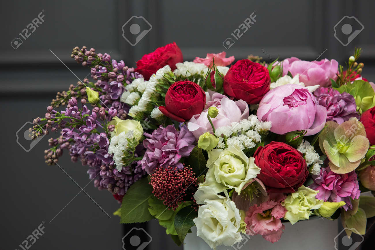 Bouquet of different beauty flowers in round present box on dark background - 126646019