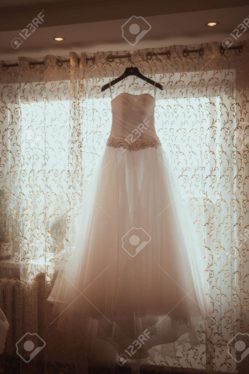 Wedding Dress Hanging In A Window Stock Photo