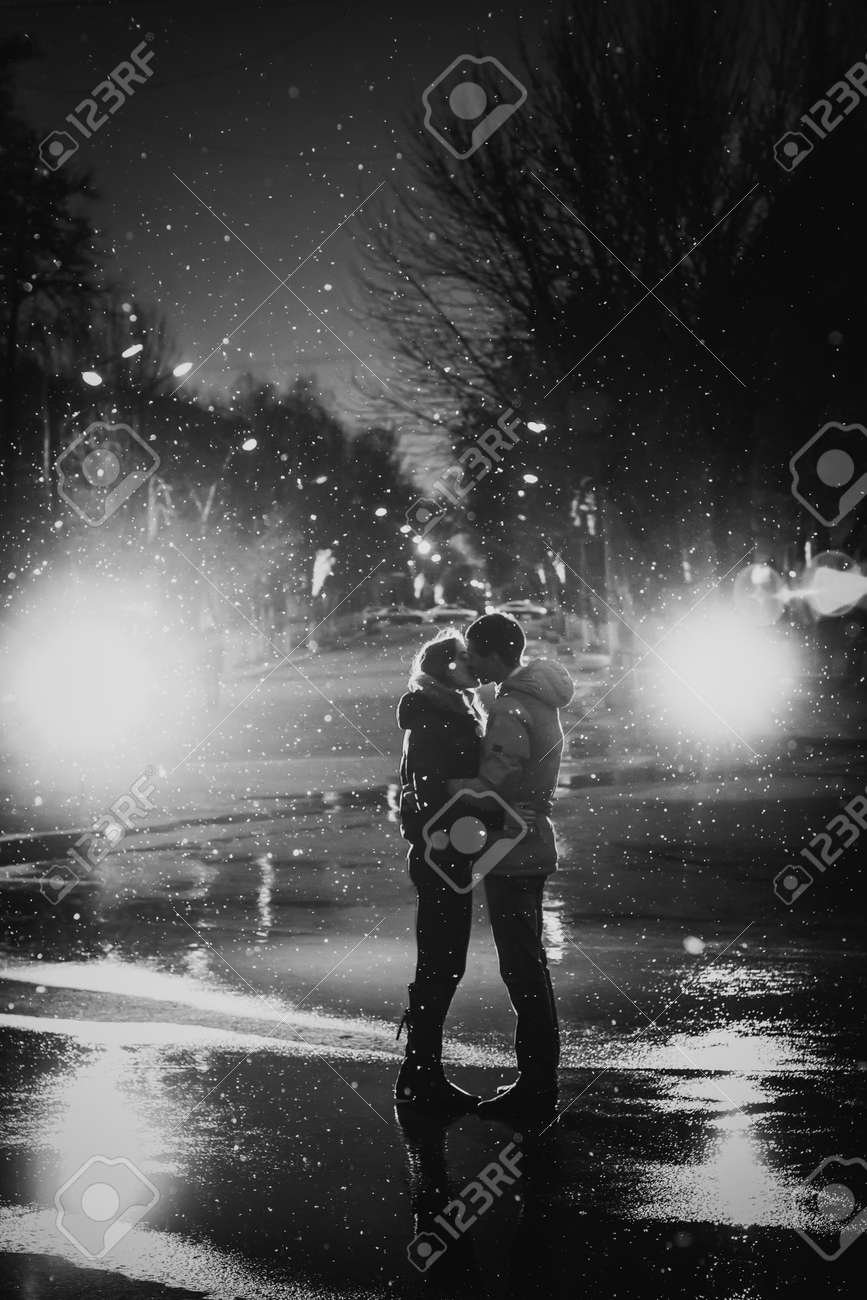 In love couple kissing in the snow at night city street black and white stock