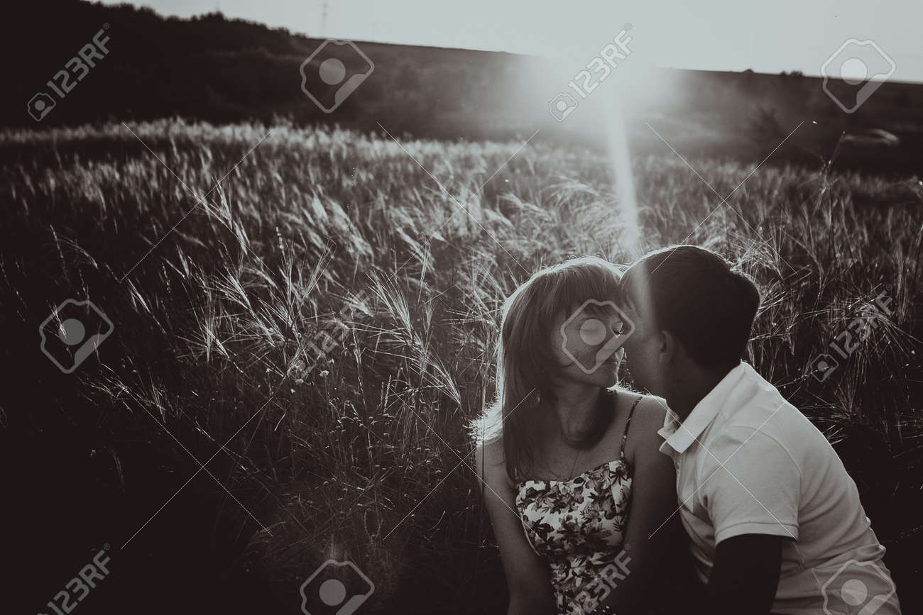 Romantic black white photo couple standing and kissing on background