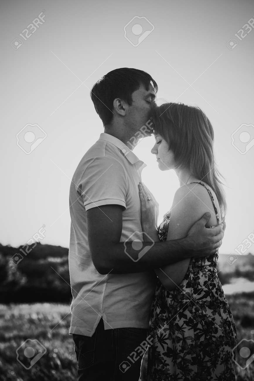 Black white photography romantic couple standing and kissing on background summer meadow sunset stock photo