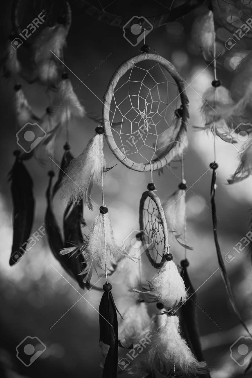 Black and white photo of a dream catcher at sunset purple dark background stock photo