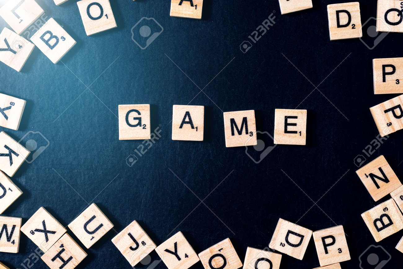 Word Game With Wooden Letters On Black Board With Dice And Letter