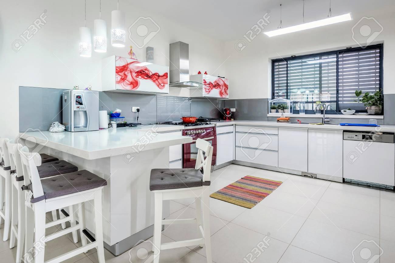 Interior de la cocina moderna con mesa de comedor, sillas, lámparas, Israel.