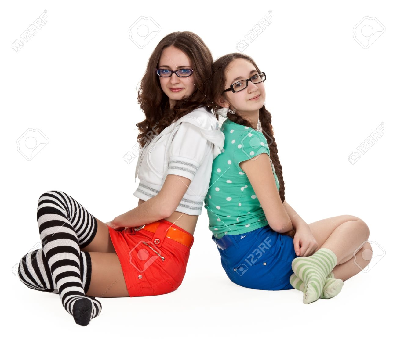 Stock Photo Two Girls Are Sitting On A White Floor In Colored Skirts And Striped Socks