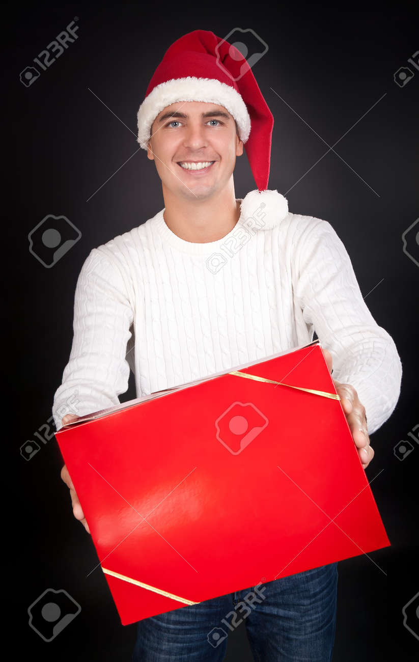 Smiling man in Santa hat gives a red box in the studio against a dark background Stock Photo - 10485649