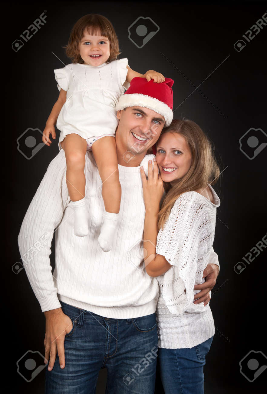 Father in santa hat holding little girl on his shoulder and hugged his wife in the studio against a dark background Stock Photo - 10485730