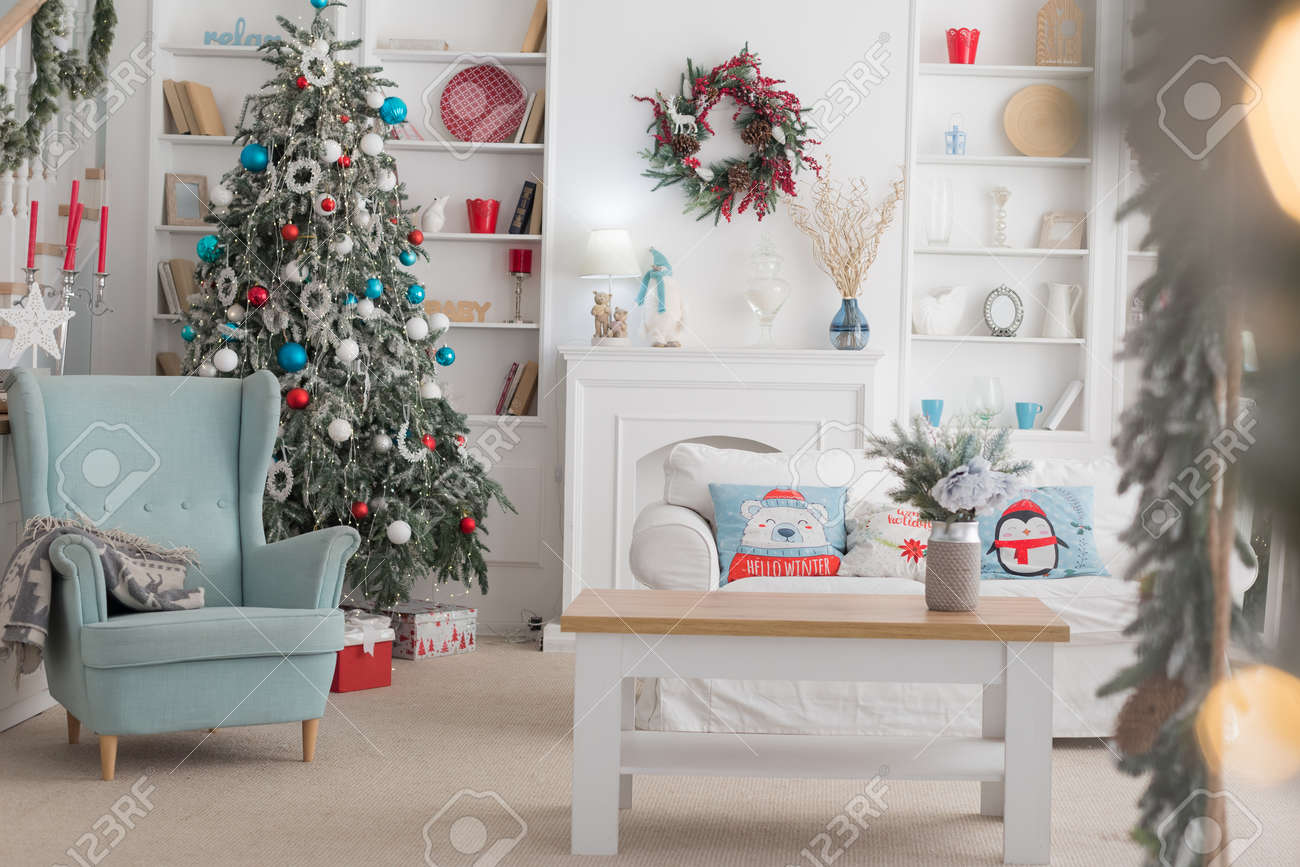 The interior of the Christmas room, a white sofa with pillows at the coffee table and a blue chair - 136133258