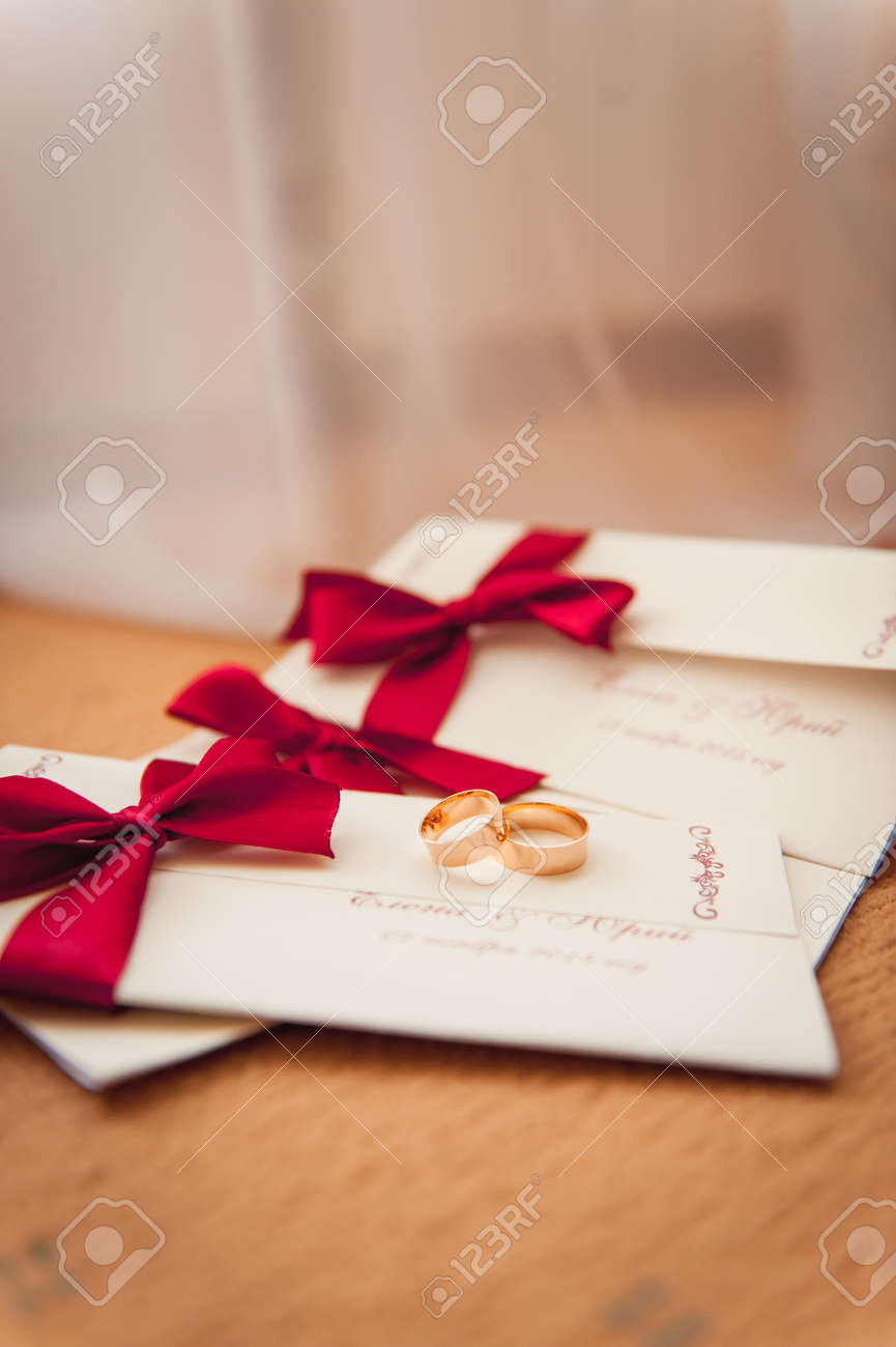 Wedding Rings On Invitation With A Red Ribbon With Bokeh Background ...