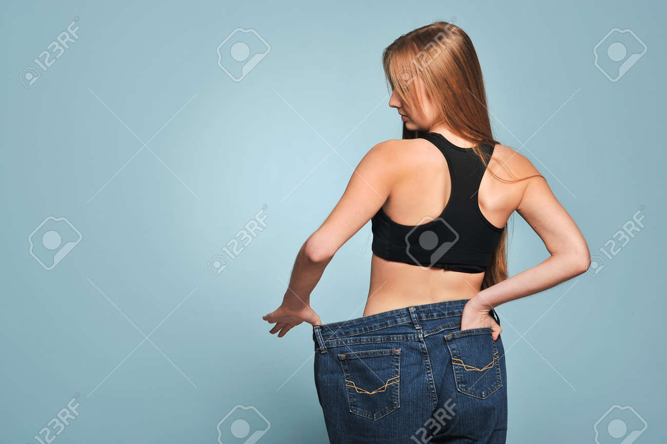 Ajuste A La Mujer Joven En Pantalones Vaqueros Flojos Despues De Perder Peso Aislado En El Fondo Azul Fotos Retratos Imagenes Y Fotografia De Archivo Libres De Derecho Image 68719291