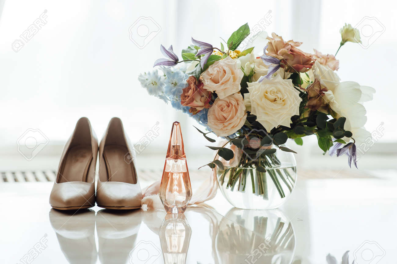 wedding set of the bride. Beige shoes, perfume and a beautiful bouquet are on the marble floor - 126509435