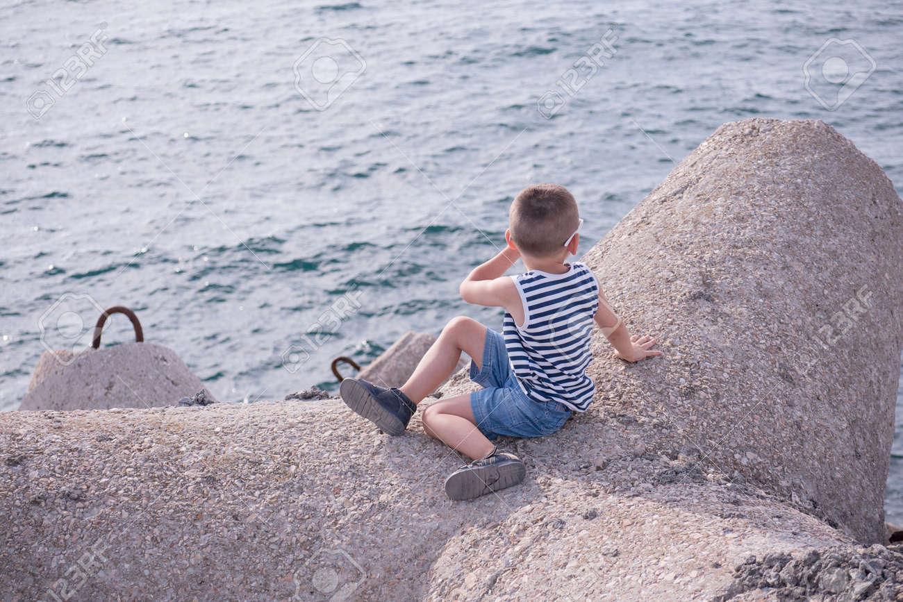 Niño Sano Vestido Con Una Camisa A Rayas Y Pantalones Cortos De Mezclilla Sentado En Rompeolas De Hormigón Junto Al Mar