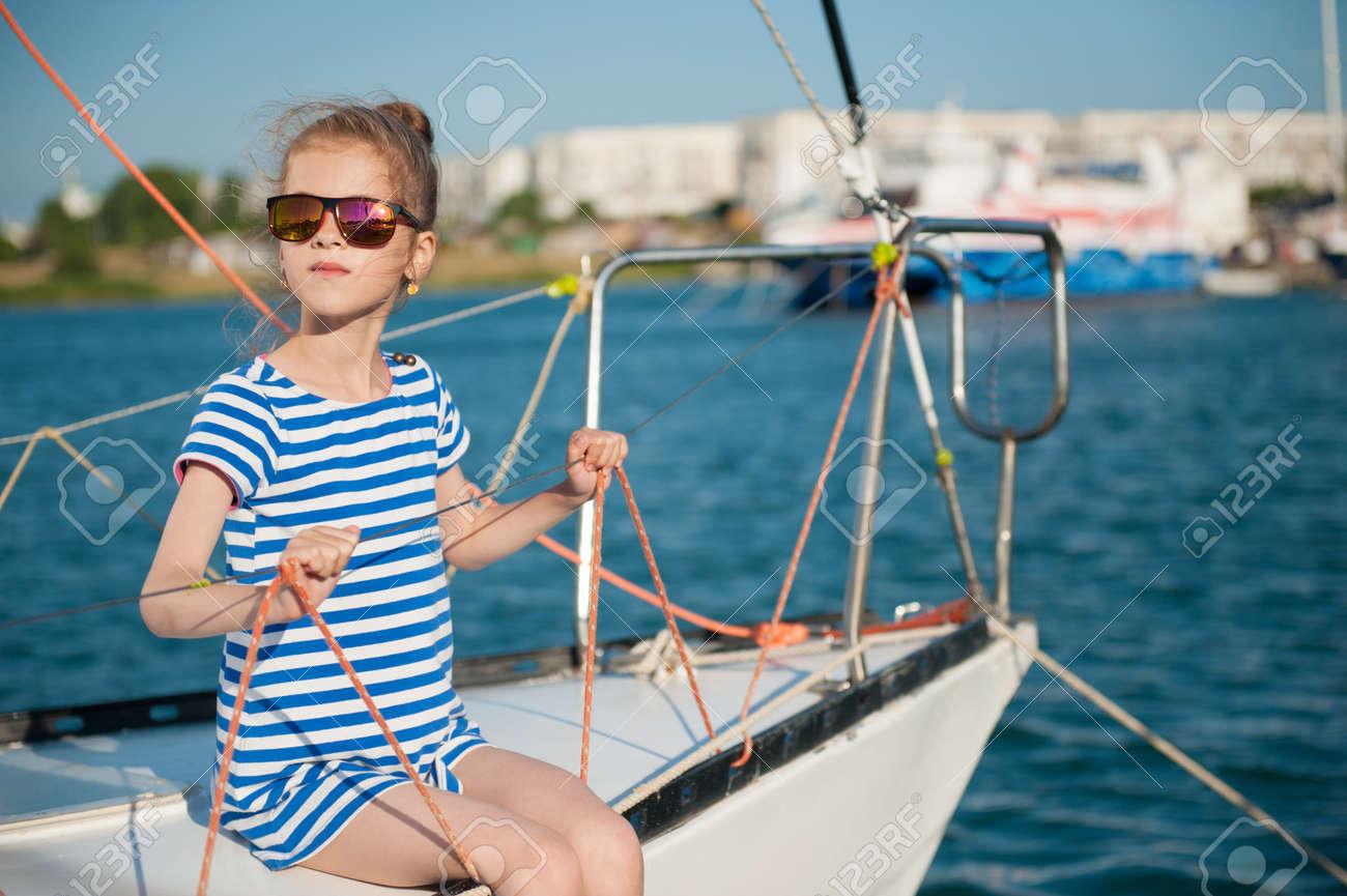 f128dca1ad Foto de archivo - Hermosa niña delgada en una camiseta de rayas y gafas de  sol sentado a bordo del lujoso yate blanco en crucero de verano