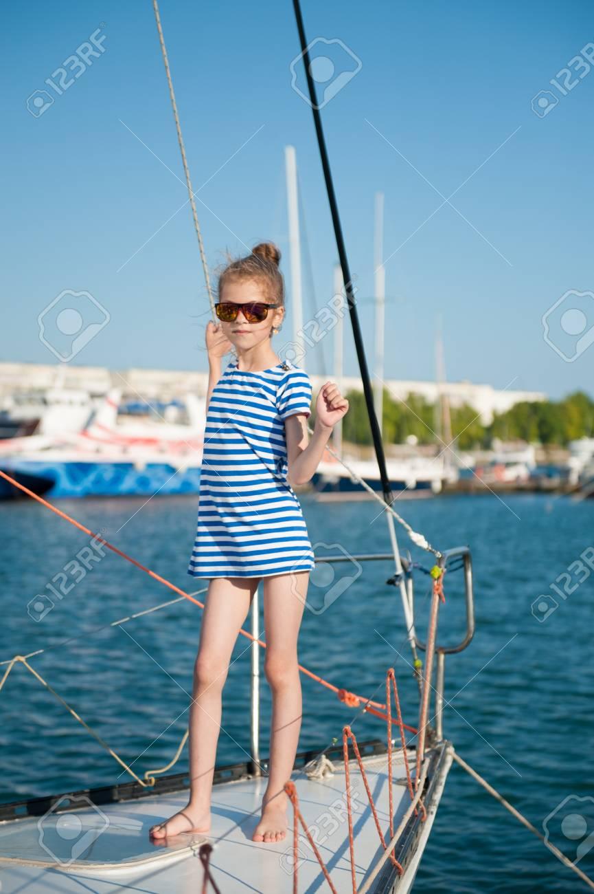 Esbelta niña hermosa en una camiseta de rayas y gafas de sol que sostienen  el barco 561b09edd55