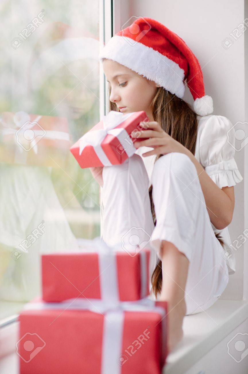 f8043bb1b7c4f adorable little girl in Santa hat dreaming by the window holding a box with  gift in