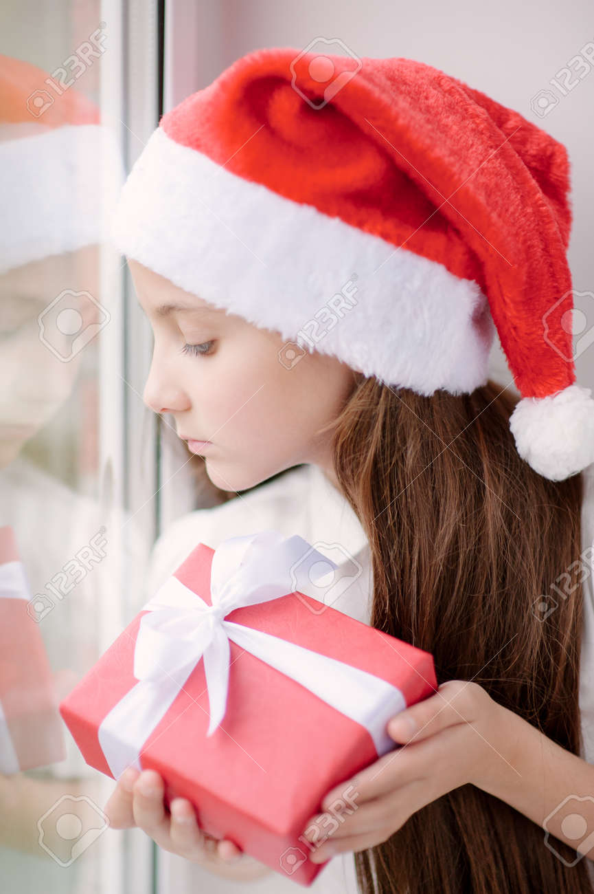 b12ce8babb6e4 cute little girl in Santa hat dreaming by the window holding a box with  present in