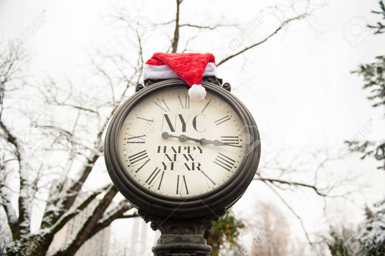 stock photo vintage street clock with inscription happy new year nyc and santa claus hat on them outdoors in winter
