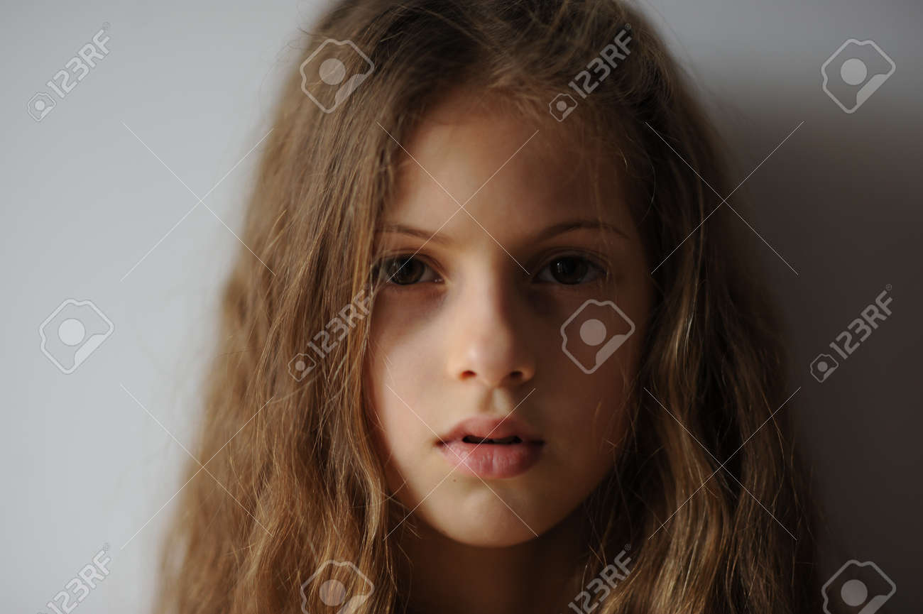 portrait of pensive beautiful little girl with long hair and serious face - 133021555
