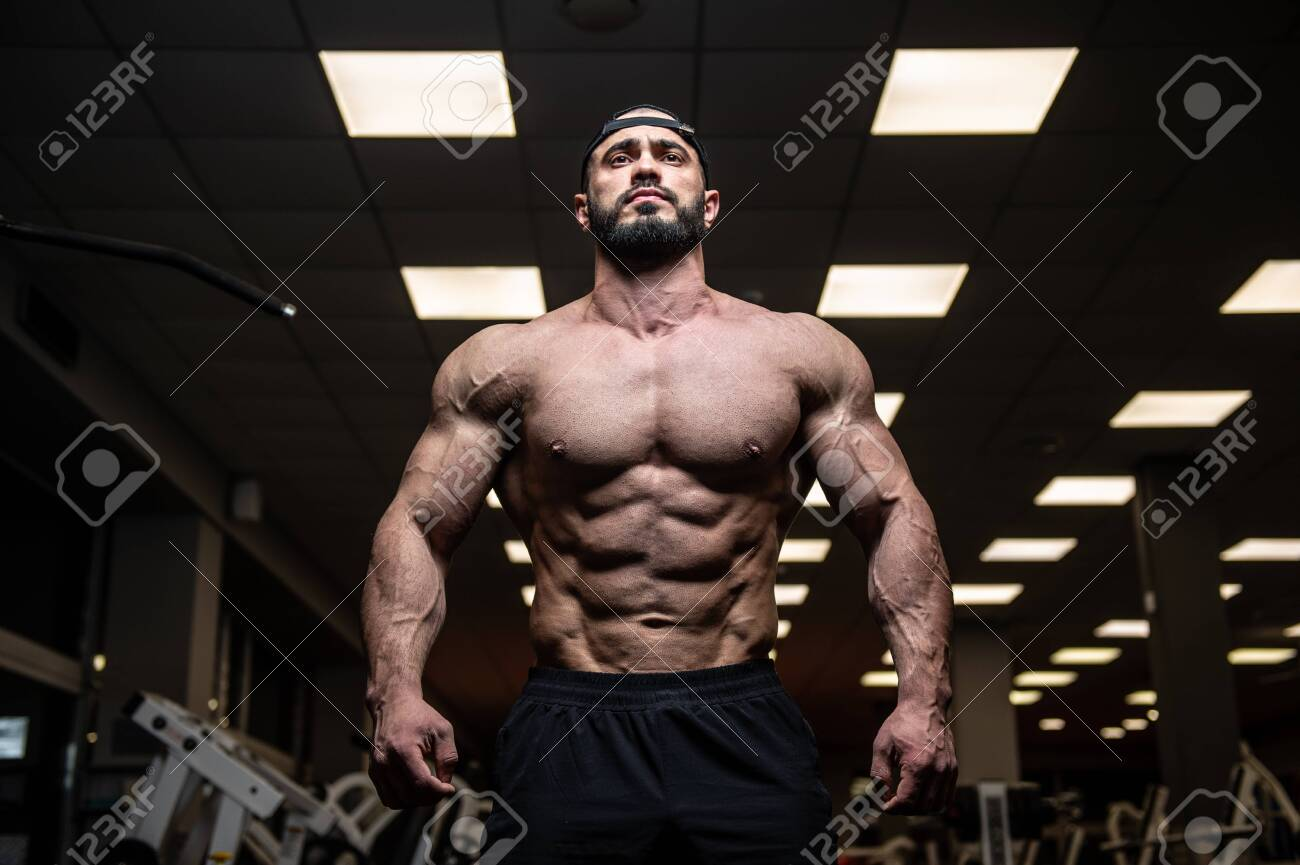 young bearded athlete with strong muscles in dark fitness club gym - 146662052