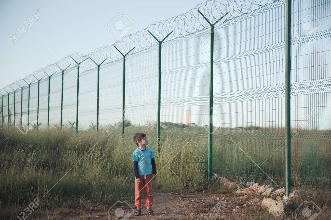 one poor little refugee orphan kid in dirty clothes standing near state border with high fence with razor barbed wire looking on it with hope - 157181854