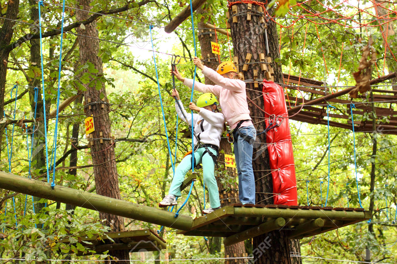 Kletterausrüstung Baum : Mutter und tochter in kletterausrüstung hindernisse zwischen hohen