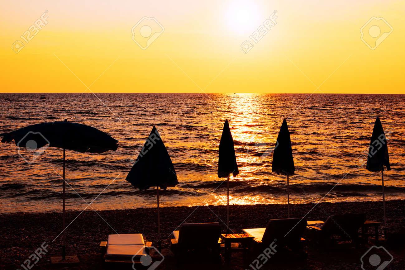 Beach umbrellas during sunset . Paradise seaside in the twilight . Summertime vacation destination - 167986656
