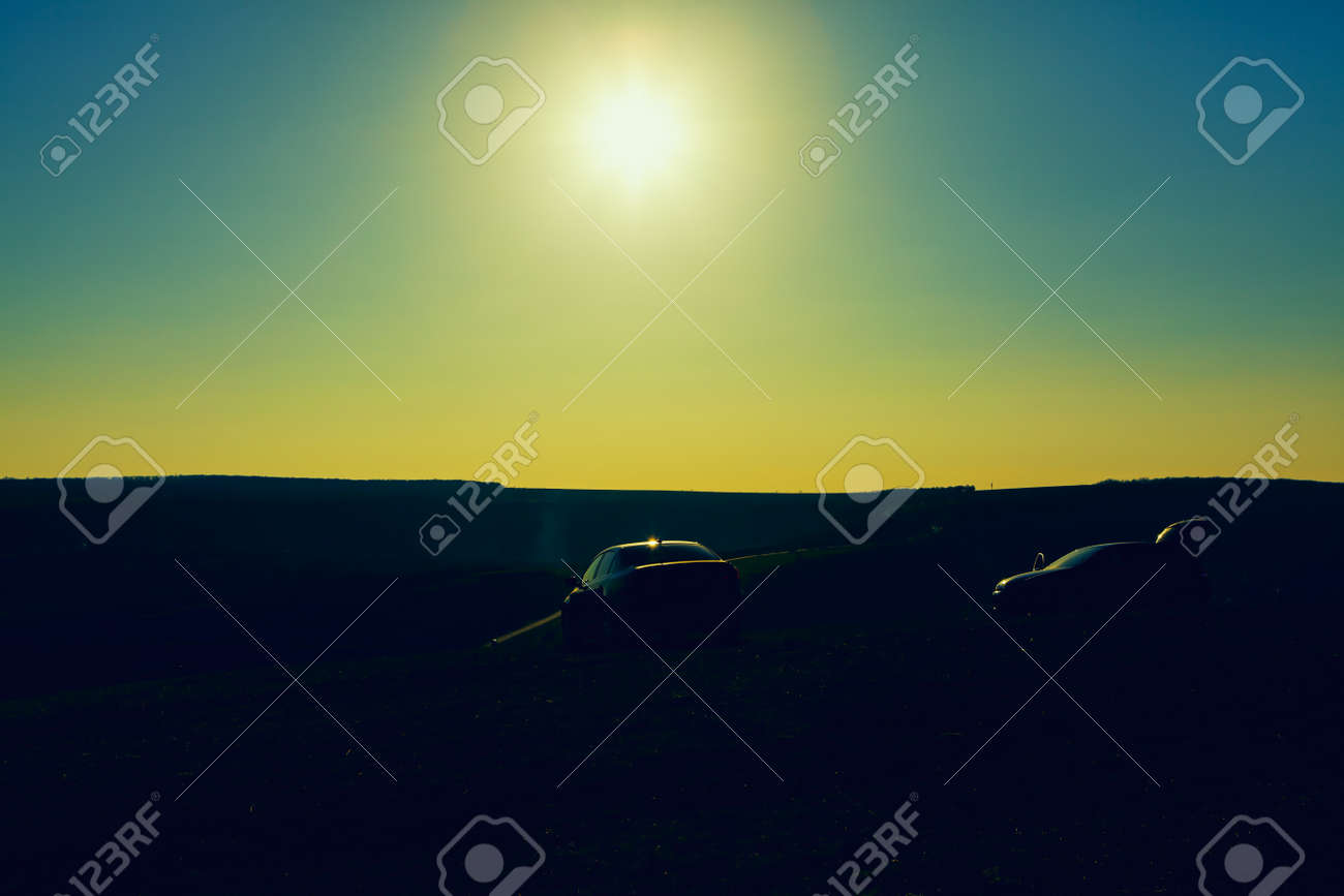 Silhouette of cars on the hill . Sundown over the country - 167986899